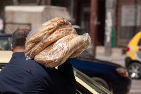 A Syrian baker is carrying  fresh made traditional flat breads in the street. The breads are stacked up and put in plastic bags. He placed the bags on his shoulder.