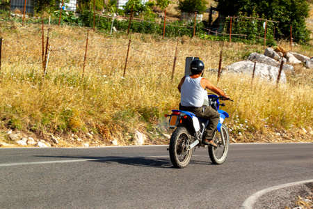 A man wearing helmet, white undershirt and khaki pants is riding a motorbike in a rural area. There are farms  by the road and he is carrying a plastic barrel in front of him between his arms. Imagens