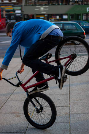 Oxford, UK 11/08/2009: A teenager boy wearing hoodie and sagging pants is doing acrobatics on a BMX bike. He is trying to jump on the front wheel of the bike on a sidewalk at city center.