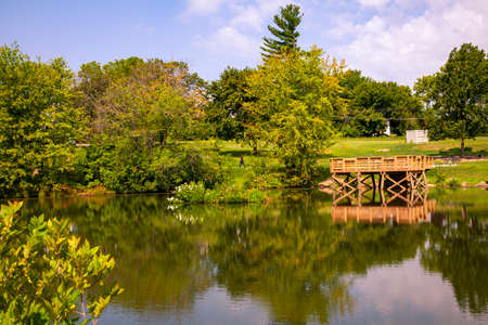 A scenic pond with a wooden fishing pier in Clarksburg. This little area is a popular hiking spot for the neighborhood. The pond is surrounded with trees and shrubs and is booming with wildlife.