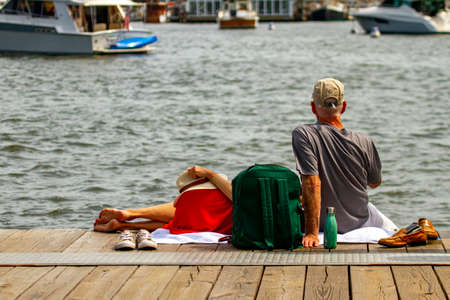 A caucasian couple is enjoying the nice weather on Annapolis. Both have taken off their shoes. The man sits with legs hanging off the wooden pier and the woman is lying on his lap.
