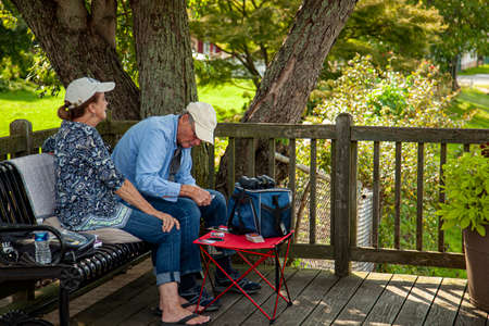 Chesapeake City, MD, USA 08/25/2020: An elderly caucasian couple wearing baseball hats shirts and jeans is sitting on pillows on a metal park bench in a wooden deck. They play cards on a small table.