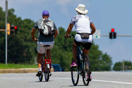 A senior couple wearing casual shorts and t shirts as well as hats is riding bikes near a highway on a sunny summer day. Man has a foldable pedal bike and the woman has a mountain bicycle.