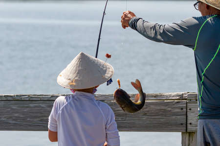An Asian boy wearing traditional Chinese bamboo straw coolie conical hat is fishing with his father on a bridge. The boy has just caught a cat fish and father helps him take it off the hook.