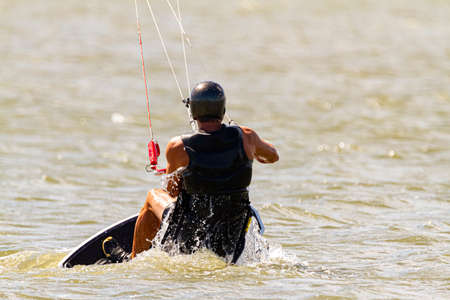 A kitesurfer wearing protective equipment is losing balance and falling off the board into the sea off the coast of Assateague Island.. He then finds a way to get back on board.