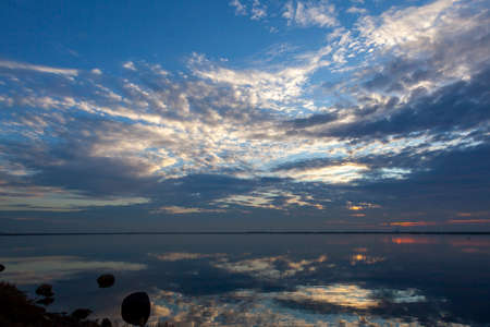 An abstract image taken at a lakefront at sunset. Image shows a spectacular cloudy sky and its reflection over water. Sky and water are separated only by a thin line of coast on the horizon.