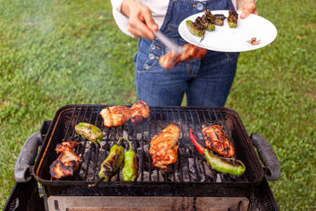a chef wearing jean overalls and white shirt is by a charcoal grill where marinated chicken slices, red and green peppers are fire grilled. She uses tongs to flip them and collect them into a plate.