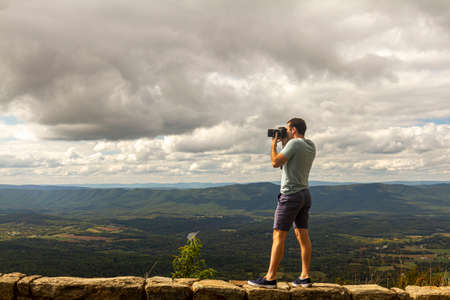 A young caucasian landscape photographer wearing short and t shirt is taking a photo of the Shenandoah Valley on top of a stone barrier wall by a cliff near a scenic overlook by the skyline drive.