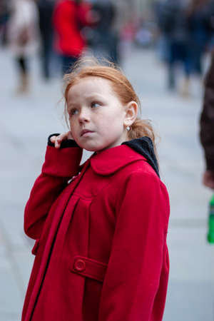 Bath, UK, 03/06/2010: street portrait of a pretty British girl with red hair, freckles, green eyes wearing a classical red winter coat. She is scratching her ear while looking at something curiously 新闻类图片