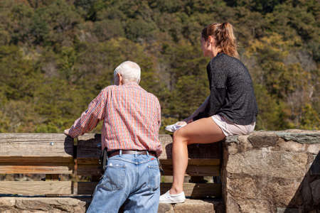 Great Falls, VA, USA 10/03/2020: An elderly man and his teen daughter are looking at the great falls, from a scenic overlook. The girl wearing shorts is sitting on stone wall despite the risk of fall