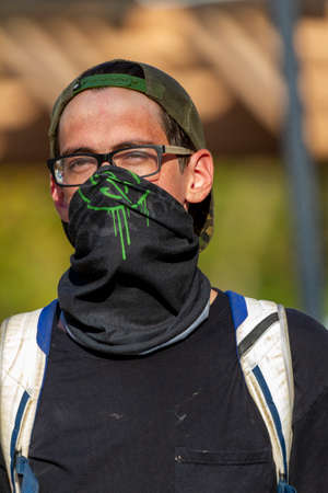 Ellicott City, MD, USA 10/07/2020: A young caucasian male wearing a base ball hat backwards and a large cloth face mask is walking in the street. He has a free spirited style