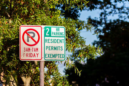 Side by side traffic signs one showing no parking on friday and the other showing 2 hours maximum parking except resident permit holders. Street parking restrictions are part of urban lifestyle.