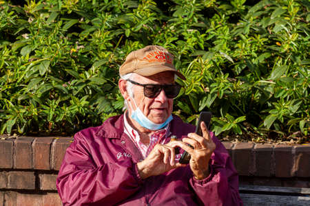 Frederick, MD, USA 10/14/2020: An elderly caucasian man is trying to dial a number on the keyboard of his old flip phone while holding a cigar between fingers. He moved his face mask under his chin.