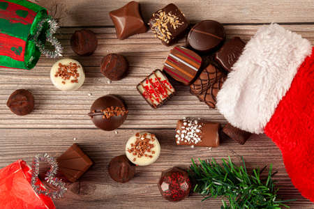 Pieces of delicious assorted chocolates are coming out of a christmas stocking on wooden table. Pine christmas tree piece with holiday gift decor are put on sides. A nice seasonal flat lay composition