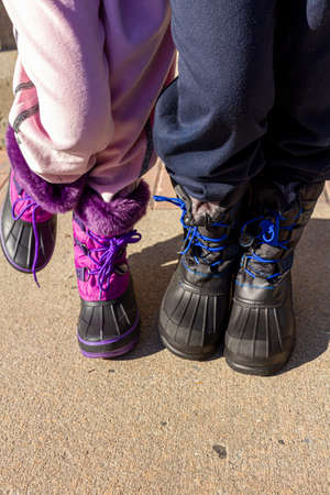 Waist down close up image of a boy and a girl are standing side by side on concrete. They wear thick waterproof winter boots and track pants. A concept image for playing outside on cold winter days.