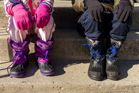 Waist down close up image of a boy and a girl are sitting side by side on concrete stairs with hands over knees. They wear waterproof winter boots and track pants coats and glove. Winter clothing.