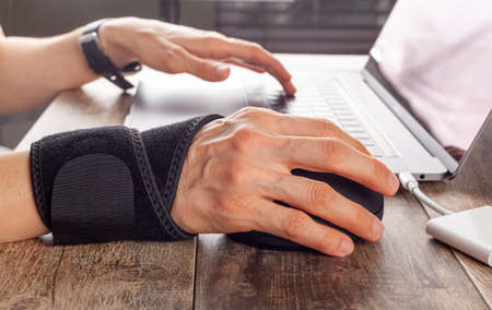 Chronic trauma to the wrist joint in people using computer mouse may lead to disorders that cause inflammation and pain. A woman working on desk uses wrist support brace and ergonomic vertical mouse Stock fotó