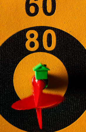 A dart board with an arrow hitting the bullseye. There is a small house icon on top of that arrow. A versatile image for competition, real estate, housing market, home buying selling and mortgage rate