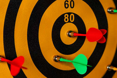 Close up image of a dart game in which one of the arrows hit the bullseye. A vibrant versatile image useful for competition, struggle, hard work, success, achievement, rivalry concepts.