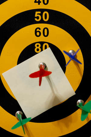 A dart board with multiple arrows. The red arrow hits the bullseye. A blank paper (sticky note) is underneath the winning arrow. A customizable image with your text can be added onto the blank paper.