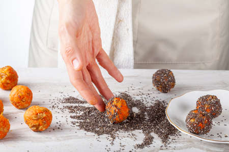 A woman chef is preparing carrot cake bliss bites in the kitchen. She dips the carrot balls into a pile of chia seeds and roll them to coat their surface. Then she moves them to plate to serve.