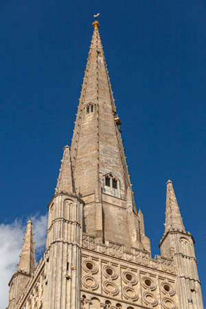 Close up isolated view of the tall tower of Famous historic Norwich cathedral whose foundations date back to 11th century. This large cathedral is dedicated to the Holy and Undivided Trinity