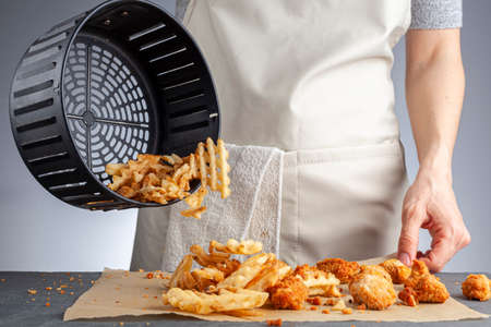A woman is dumping fresh made potato waffle fries from basket onto a countertop together with chicken nuggets. She fried them in air fryer using very little fat. A healthy homemade convenient snack.