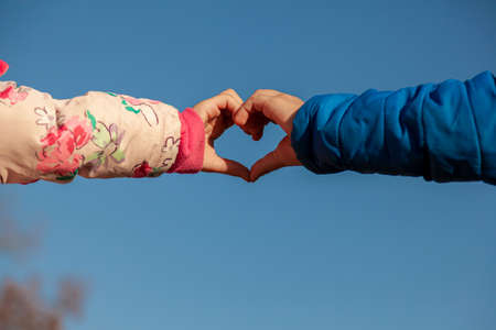 A cute abstract image showing the touching hands of a girl with pink coat and a boy with blue coat. Hands make heart shape against clear sky. A concept image for innocent love, valentines day, romance Banque d'images