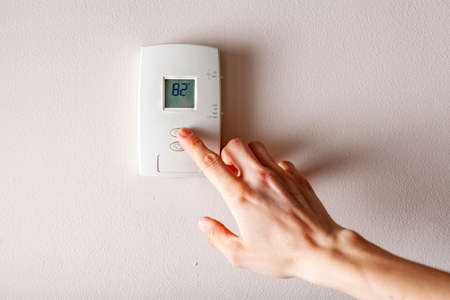 A woman is pressing the up button of a wall attached house thermostat with digital display showing the temperature. A concept image for electricity bill, heating, cooling, eco friendly, saving etc.