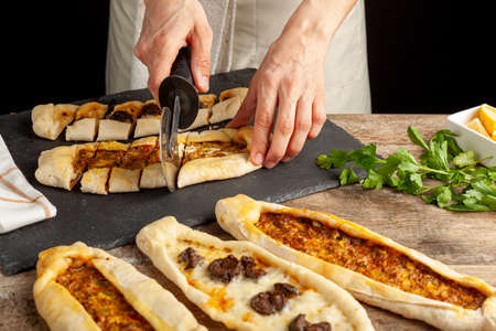Kasarli sucuklu pide and kiymali pide are traditional Turkish flatbreads similar to pizza with meat and cheese toppings. They are served with lemon and parsley leaves. A woman is slicing them.