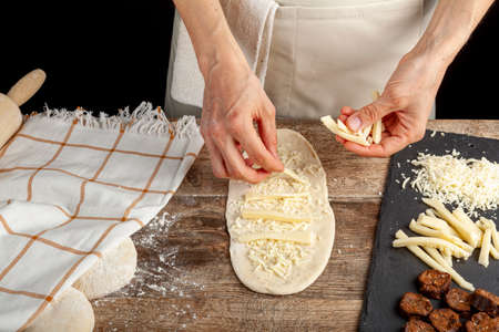 a flattened dough on wood kitchen countertop. A bread making concept image with loafs, cheese and sucuk in back. Turkish kasarli sucuklu pide recipe. A caucasian woman is placing cheese slices on it.