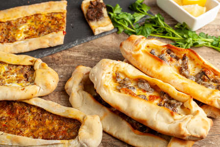 Kasarli sucuklu pide and kiymali pide are traditional Turkish flatbreads similar to pizza with meat and cheese toppings. They are served with lemon and parsley.