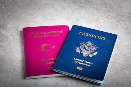 Image of a US passport and a Turkish passport side by side. Concept image for immigration to USA, path to citizenship, dual citizen, living abroad and the application process for being a US citizen. Foto de archivo
