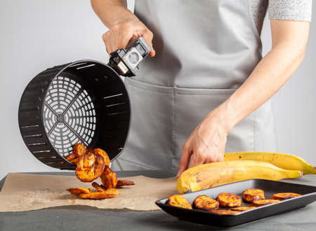 A caucasian woman is pouring freshly made plantain chips (Platanos Maduros) onto baking paper for cooling. She holds the handle of air fryer basket. Air fryer makes it low calorie compared to regular. Banco de Imagens