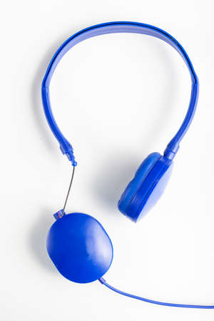 Isolated image of a blue headphone with adjustable head band. One of the ear pieces is broken at the connection side with wires exposed. Concept image for non recycable electronics pollution and waste