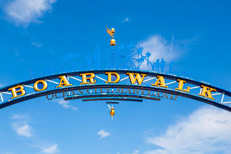 close up isolate image of the wooden arch at the entrance of famous board walk by the Ocean City, Maryland beach A popular tourist spot on east coast of USA The arch is against blue sky with clouds.