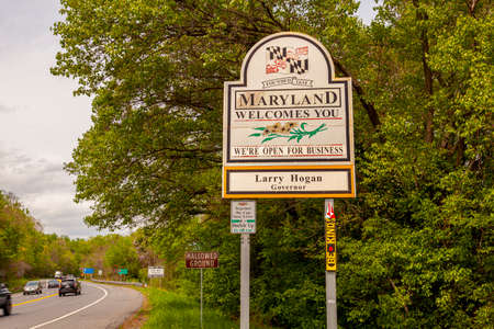 Maryland Welcomes You road sign on the scenic byway US Route 15 at the border of Maryland and Virginia. It has MD flag and says open for business.