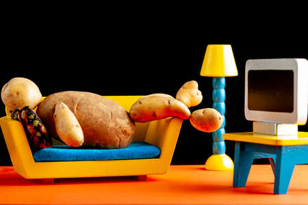 A quirky metaphorical concept image showing a potato man lying on a couch watching tv in a living room setting. Image for being couch potato, obesity, sedentary lifestyle and health effects.