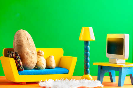 A quirky metaphorical concept image showing a potato family lying on a couch watching tv in a living room setting. Image for being couch potato, obesity, sedentary lifestyle and health effects.