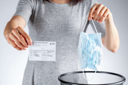 Clarksburg, MD, USA 05-16-2021: CDC announced the lifting of face mask requirement for fully vaccinated individuals. A woman showing vaccination record card is removing her face mask and discarding it