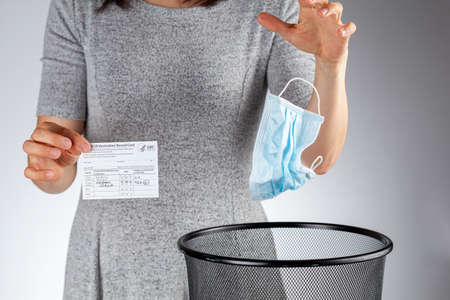 Clarksburg, MD, USA 05-16-2021: CDC announced the lifting of face mask requirement for fully vaccinated individuals. A woman showing vaccination record card is removing her face mask and discarding it Editorial