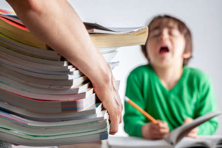 Ambitious parenting with high academic achievement expectations from kids concept. A mother is bringing a pile of test prep books to her bored, tired kid who is crying and protesting during homework
