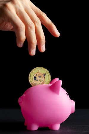Concept image for using digital crypto currency for savings. A caucasian woman is putting a symbolic dogecoin coin into a piggy bank as a saving modality. Isolated image against dark background