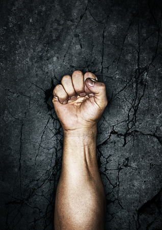 Protest fist,  grungy fist raised in protest against cracked stone background
