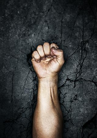 puños cerrados: Protesta puño, puño sucio levantó en protesta contra el fondo de piedra agrietada