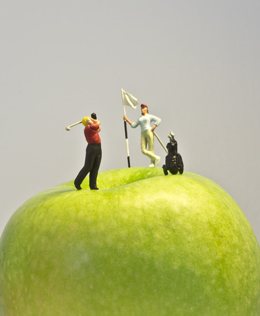 Miniature golf on apple  Macro shot of golfing figurines playing round on top of green apple
