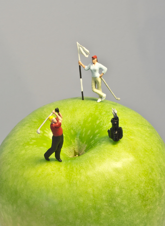 그린 애플의 상단에 라운드 재생 골프 인형의 사과 매크로 샷 미니어처 골프