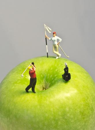 Minigolf sulla mela Macro colpo di figurine golf giocare rotonda sulla cima di mela verde Archivio Fotografico - 44445352