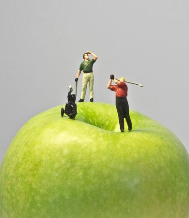 애플에 미니어처 골프 녹색 사과 꼭대기에 재생하는 인형 골프의 매크로 샷
