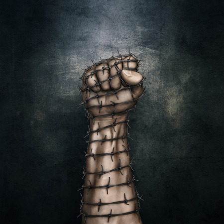 Barbed wire fist / 3D illustration of grungy raised fist wrapped in barbed wire against dark stone background Archivio Fotografico